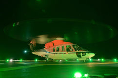 The helicopter night landing on offshore oil rig. Platform Stock Image