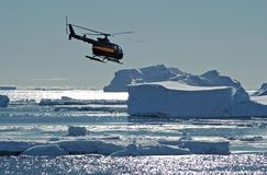 Helicopter over Antarctic icebergs. A helicopter is flying over an Antarctic iceberg scenery in backlight. Picture was taken during a 3-month research expedition Stock Photos