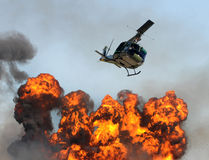 Helicopter over fire. Helicopter flying over giant explosion and fire royalty free stock photo