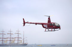 Helicopter over sailing ships Stock Images
