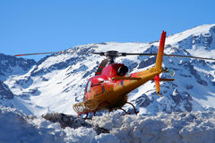 Helicopter over snowy mountain Stock Image