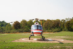 Helicopter parked at the helipad near forest. Royalty Free Stock Photo
