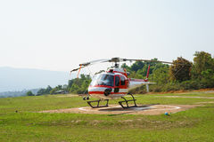 Helicopter parked at the helipad near forest Stock Photos