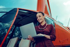 Beaming good-looking businesswoman in red shirt and bulky jewelry royalty free stock images