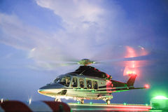 Helicopter parking landing on offshore platform. Helicopter transfer crews or passenger to work in offshore oil and gas industry. Night flight training of Pilot Stock Photos