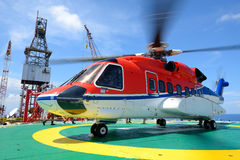 Helicopter pick up passenger on the offshore oil rig platform Royalty Free Stock Photo
