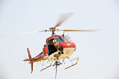 Helicopter picking up cargo. Helicopter closeup hovering above field to pick up cargo, motion blur on rotor Stock Images