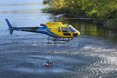 Helicopter picking up water during fire fighting operations Stock Image