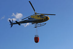 Helicopter picking up water during fire fighting operations Royalty Free Stock Images