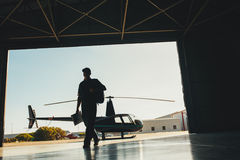 Helicopter pilot arriving at airplane hangar stock image