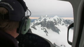 Helicopter pilot flies to helipad in snowy mountains in New Zealand. New Zealand, 12 October 2013: Helicopter pilot flies to helipad in snowy mountains. Scenic stock video