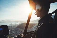 Helicopter pilot flying aircraft over a city. Close up of a helicopter pilot flying aircraft over a city on a sunny day Stock Images