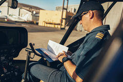Helicopter pilot reading a manual book royalty free stock image