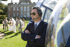 Helicopter pilot in sunglasses by helicopter, wedding party in background Stock Photo