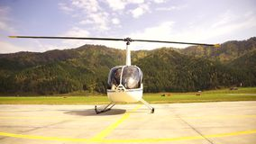 Helicopter is preparing to take off, the pilot closes the door. Small lightweight aviation. bottom view on a propeller