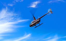 Helicopter R44 Clipper. Helicopter flying under a blue cloudy sky - Robinson R44 Clipper II royalty free stock image