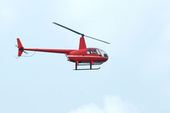 Helicopter. A red miniature sightseeing helicopter in the sky Stock Images