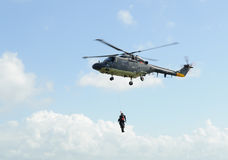 Helicopter rescue. Flying rescue helicopter hoisting and rescuing two people stock photos