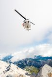 Helicopter with a rescuer standing on its ledge Royalty Free Stock Photos