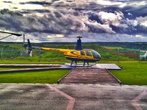 Helicopter Robinson R-44, Leaden clouds,. Yellow helicopter Robinson R-44 at the landing site, ready to take off. Leaden clouds, on a helipad Royalty Free Stock Image