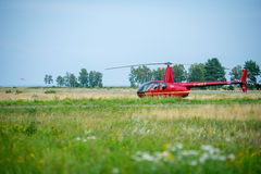 Helicopter Robinson R44 in a meadow near Nida airoport. Royalty Free Stock Photography