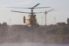 Helicopter  scooping water Royalty Free Stock Photos
