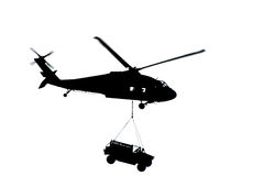 Helicopter Silhouette. Silohuette of a helicopter transporting a military truck royalty free illustration