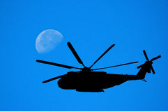 Helicopter Silhouette against. Military Sikorsky VH3 Sea King Helicopter Silhouette against Moon and Sky Stock Photo