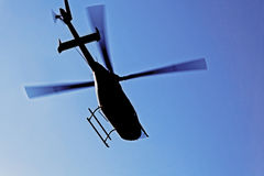 Helicopter silhouette in flight stock images