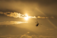 Helicopter silhouette flying in the cloudy sky, stunt aerobatic show, sunset and sun rays. Stock Photos