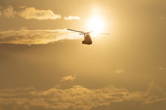 Helicopter silhouette flying in the cloudy sky, stunt aerobatic show, sunset and sun rays Royalty Free Stock Images