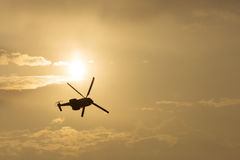 Helicopter silhouette flying in the cloudy sky, stunt aerobatic show, sunset and sun rays. Stock Image
