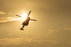 Helicopter silhouette flying in the cloudy sky, stunt aerobatic show, sunset and sun rays. Royalty Free Stock Images