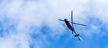 Helicopter in the sky. Helicopter flying in the blue cloud sky stock image