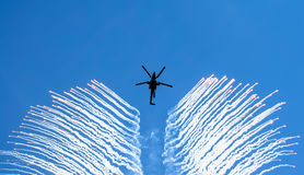 Helicopter smoke a rocket, in the sky a heat trap. Royalty Free Stock Photography