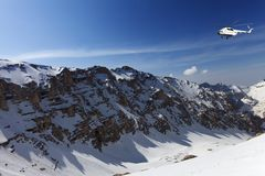 Helicopter in snowy sunny mountains Royalty Free Stock Images
