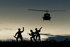 Helicopter and soldier silhouette. Multicolored sunset photo as background Royalty Free Stock Images