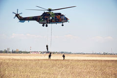 Helicopter and soldiers in action Stock Images