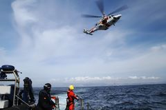 Helicopter of the Spanish Maritime Rescue Team. The helicopter of the Spanish Maritime Rescue Team  Salvamento Maritimo training over the deck of a coast guard Royalty Free Stock Images