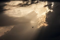 Helicopter in stormy sky stock photo