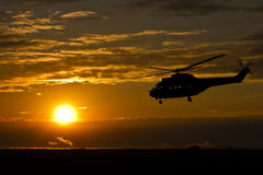 Helicopter at sunset. Helicopter flying low in sunset colors Royalty Free Stock Photos