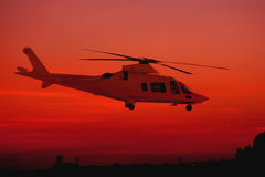 Helicopter during Sunset. A helicopter during sunset in red and pink light stock photos