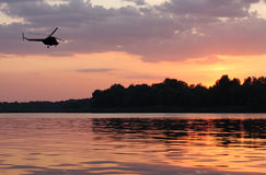 Helicopter in the sunset sky Royalty Free Stock Photos