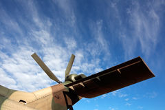 Helicopter tail rotor. Tail rotor and tail wing of a military helicopter against a blue sky with clouds Stock Photos
