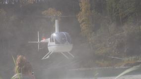 Helicopter take-off from riverbank in a mountainous area. low-flying helicopter in the highlands. Small lightweight