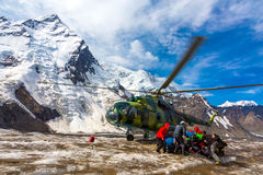 Helicopter Taking Off Ice Field of Massive Glacier and People Holding Luggage Stock Image