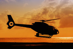 Helicopter taking off at sunset Stock Image