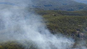 Helicopter and trees. A full shot of a helictopter and trees with smoke. Camera moves to the right stock footage
