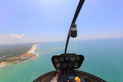 Helicopter. Robinson R44 view inside the cabin flies over the ocean Stock Image