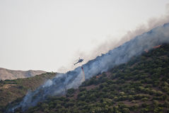 Helicopter vs fire in Sardinia. A firefighting helicopter drops water on a hill fire Royalty Free Stock Image